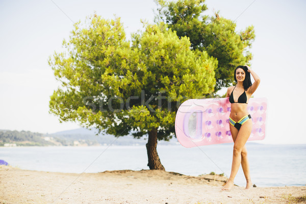 Young slim brunette woman sunbathe with an air mattress on the b Stock photo © boggy