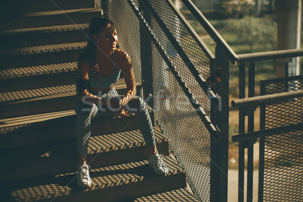 Young female runner resting on the stairs Stock photo © boggy