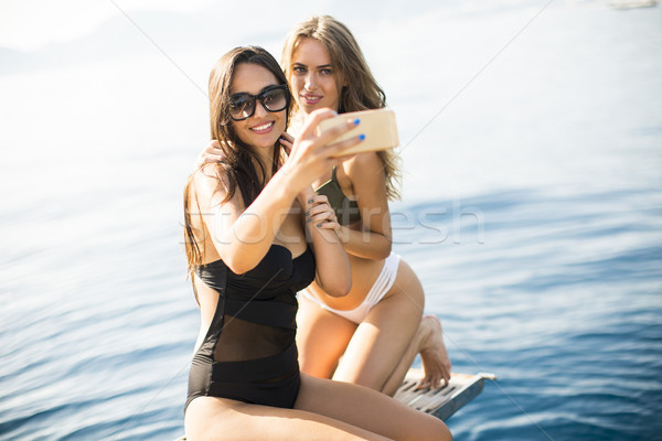 Two pretty young women taking selfie on vacation at the yacht Stock photo © boggy