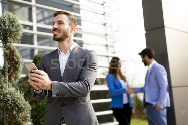Young man with mobile phone by office building Stock photo © boggy