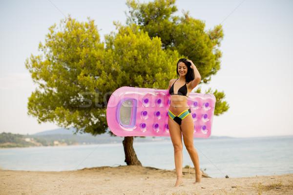 Jeune femme matelas plage joli femme eau Photo stock © boggy