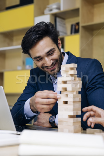 Team of young business people build a wooden construction Stock photo © boggy