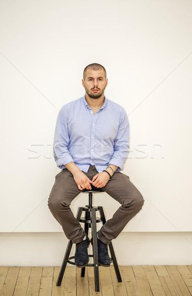 Férfi pózol zsámoly fehér fal divat Stock fotó © boggy