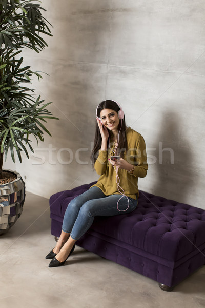 Portrait of smiling woman sitting and listening to music on head Stock photo © boggy