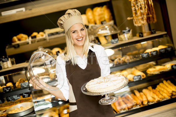 Bakery female worker posing with apple tart in baker shop Stock photo © boggy