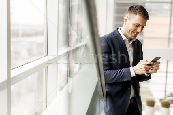 Elegant young businessman using cellphone on  staircase in offic Stock photo © boggy