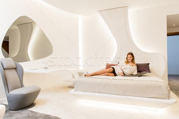 Młoda kobieta czytania katalog bed biały sypialni Zdjęcia stock © boggy