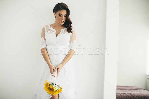 Gyönyörű menyasszony pózol esküvői ruha tart fiatal Stock fotó © boggy