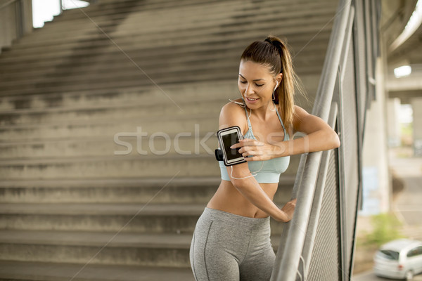Pretty young female runner resting Stock photo © boggy