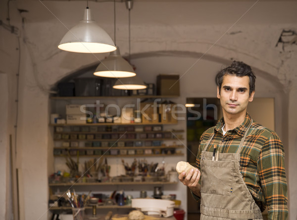 Handsome young man posing in pottery workshop Stock photo © boggy
