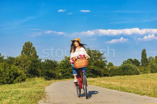 Young smiling woman rides a bicycle in counrtyside Stock photo © boggy