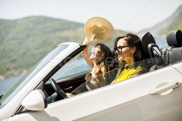 Pretty young women in white cabriolet car Stock photo © boggy