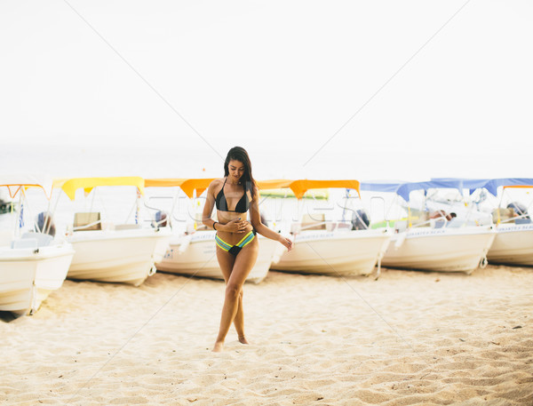 Fit and sporty woman in a swimsuit relaxing on a beach at summer Stock photo © boggy
