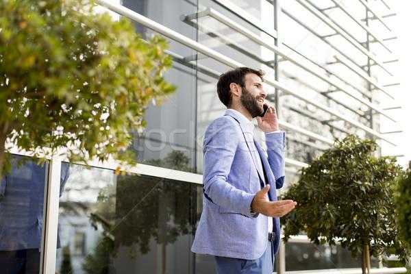 Joven teléfono móvil edificio de oficinas guapo teléfono ciudad Foto stock © boggy
