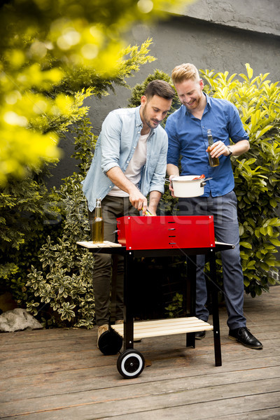 Two young men preparing  barbecue in the courtyard Stock photo © boggy