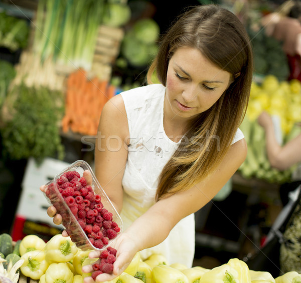 Young woman buys raspberries at the market Stock photo © boggy