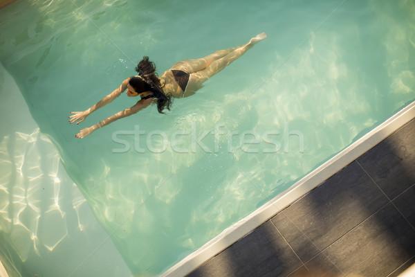 Woman in bikini  floating on water in the pool Stock photo © boggy