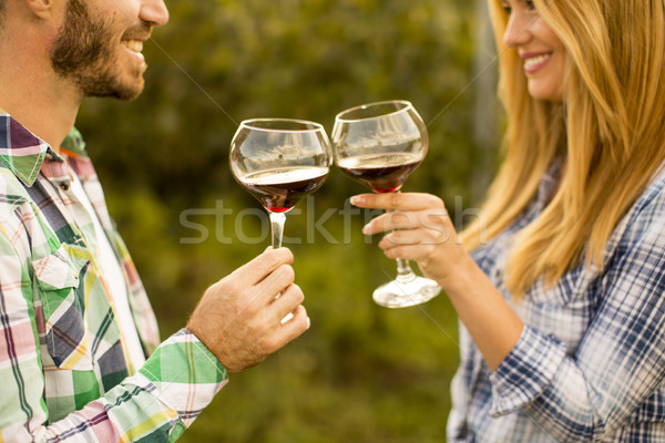 Young couple with glasses of red wine in the vineyard Stock photo © boggy