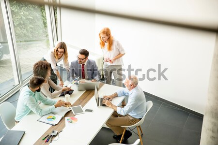 Stock photo: Joyful multiracial business team at work in modern office