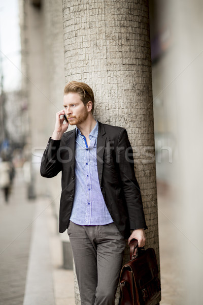 Ginger businessman waiting for transportation and using mobile p Stock photo © boggy