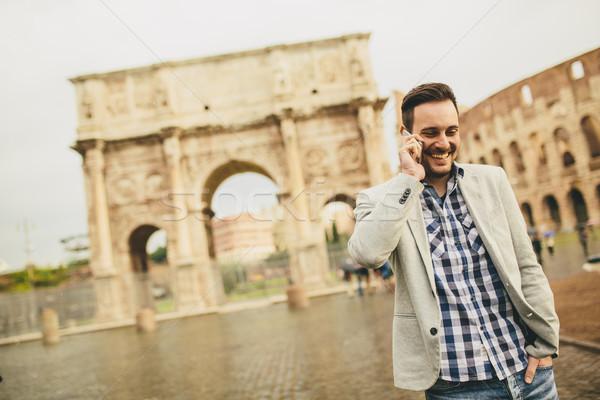 Fiatalember mobiltelefon utca Róma Olaszország üzlet Stock fotó © boggy