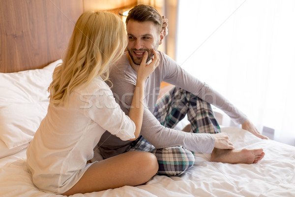 Young adult heterosexual couple on bed in bedroom Stock photo © boggy
