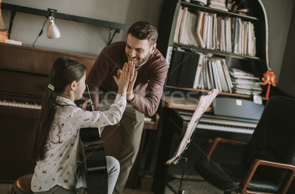 Cute little girl with guitar teacher in the room Stock photo © boggy