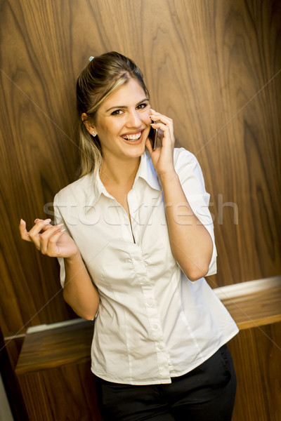 Stock photo: Young woman using mobile phone in office