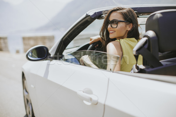 Young woman with sunglasses driving her convertible top automobi Stock photo © boggy