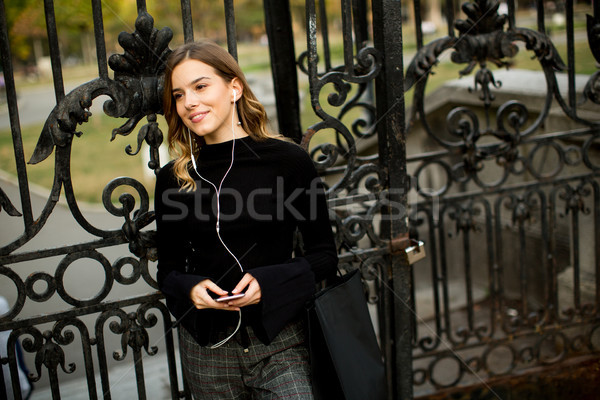 Modern young shopaholic woman by fence Stock photo © boggy