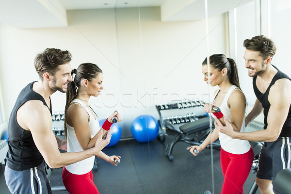 Young woman in gym exercising with her personal trainer Stock photo © boggy
