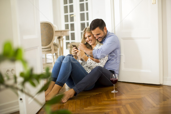Young couple sits on the floor, drinking red wine and woman usin Stock photo © boggy