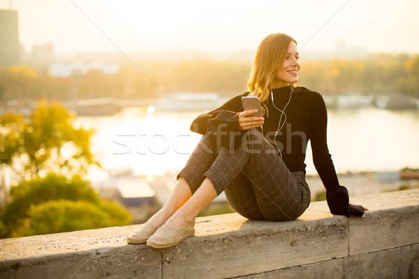 Trendi fiatal nő hallgat zene okostelefon szabadtér Stock fotó © boggy