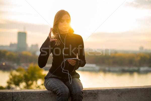 ストックフォト: トレンディー · 若い女性 · リスニング · 音楽 · スマートフォン · 屋外