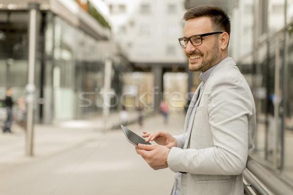 Fiatal üzletember digitális tabletta irodaház jóképű Stock fotó © boggy