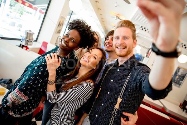 Grup gençler cep telefonu mutlu lokanta Stok fotoğraf © boggy