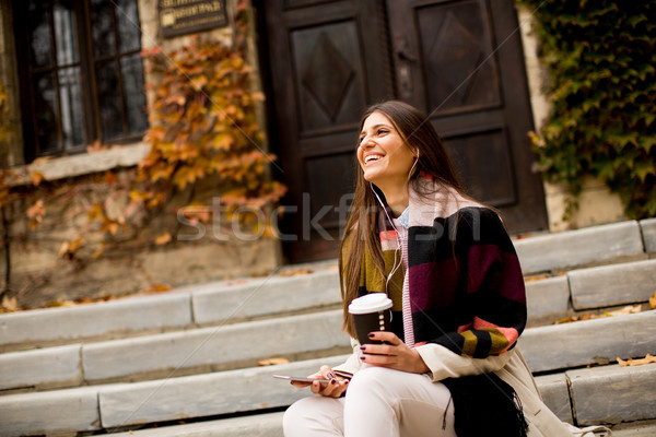 Woman sitting outside, drinking coffee to go and holding a mobil Stock photo © boggy