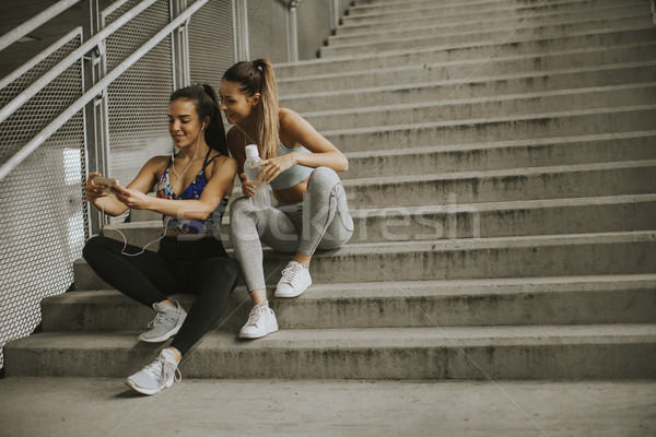 Two female runners looking on smart phone an rest after jogging Stock photo © boggy