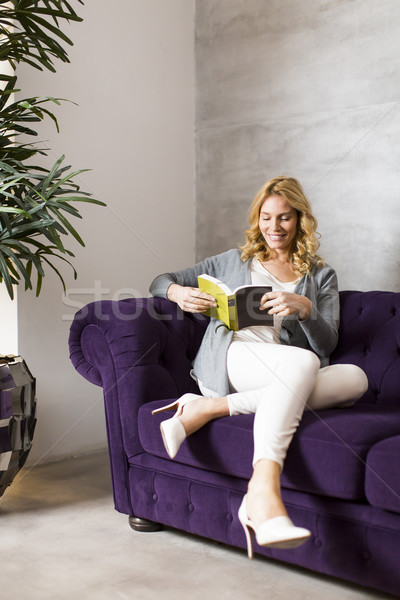 Woman reading book on sofa Stock photo © boggy
