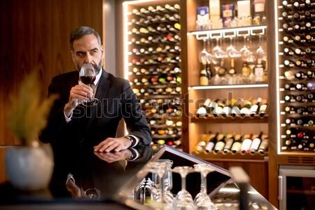 Gut aussehend reifer Mann Verkostung Rotwein Glas Wein Stock foto © boggy
