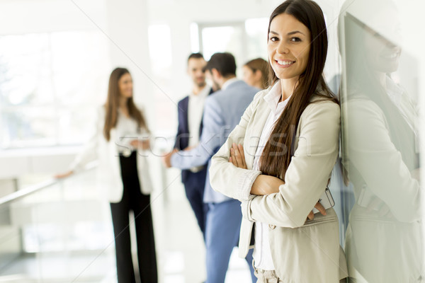 Businesswoman posing while others business people talking in the Stock photo © boggy