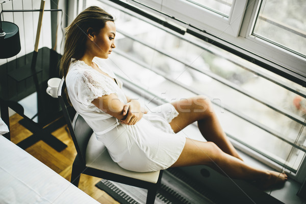 Young woman sitting and dreaming on a chair by the window in her Stock photo © boggy