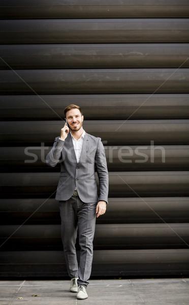 Knap jonge man mobiele telefoon kantoorgebouw jonge zakenman Stockfoto © boggy