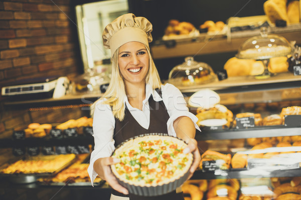 Young female baker standing in the bakery and  shows pizza Stock photo © boggy