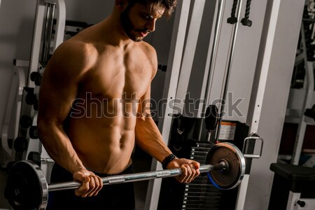 Strong and handsome young man doing exercise with dumbbells Stock photo © boggy
