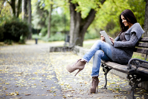 Young woman with tablet on the bench Stock photo © boggy
