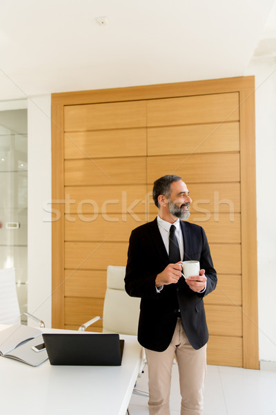 Middle-aged businessman having coffe break in modern office Stock photo © boggy