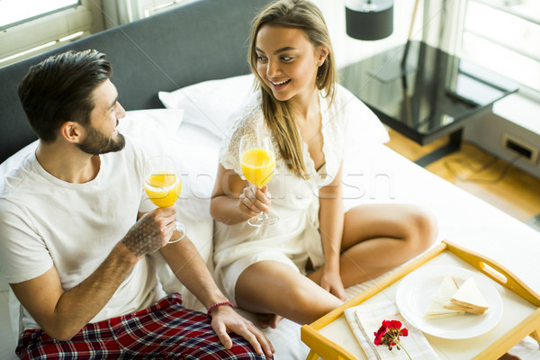 Stock photo: Happy couple in love having romantic breakfast in bed