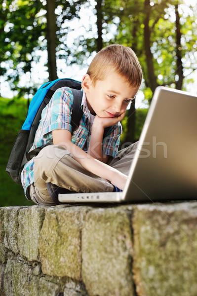 Chanceux garçon portable affaires sourire livre Photo stock © bogumil