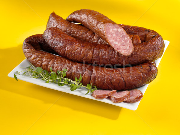Baked sausages on a plate and yellow background. Tasty kielbasa Stock photo © bogumil